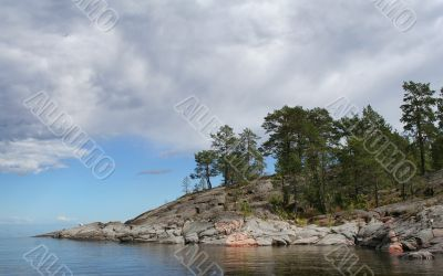 Rocky island with pines on tranquil lake