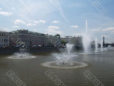 Fountains on the river in summer day