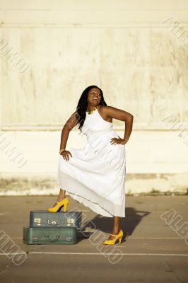 African American woman with suitcases laughs