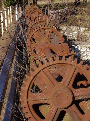 long row of rusty cog wheels
