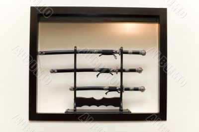 Three japanese swords on pedestal in the illuminated niche