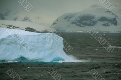 Iceberg glowing in an overcast dawn