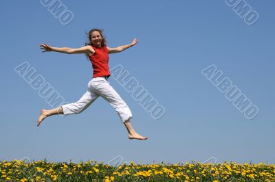 Girl flying in a jump over dandelion field