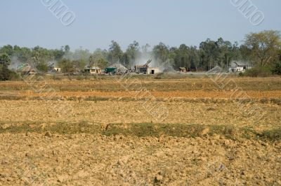 open field with view on stone industry,  india