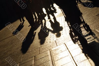 Shadows of people walking on the city street