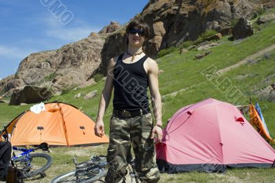 Teenager in sport trip with bicycle and tent