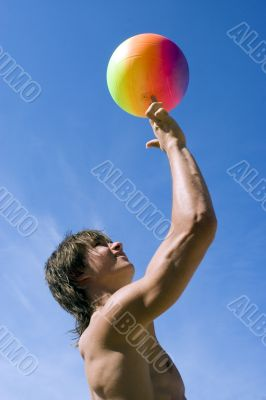 Happy sport build teenager boy with ball in beach