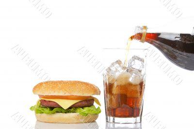 Cheeseburger and pouring soda