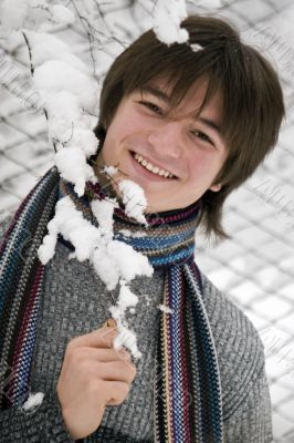Pretty  European teens boy with snown branch