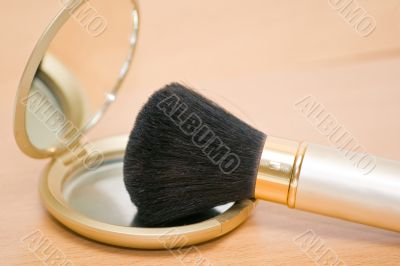 Brush for makeup reflected in mirror on wooden table