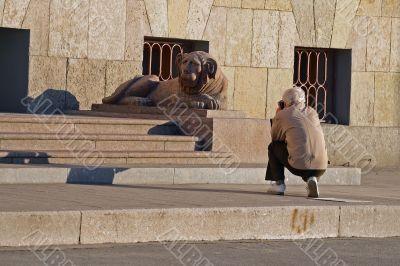 Hiker take a photograph granite sculpture lion