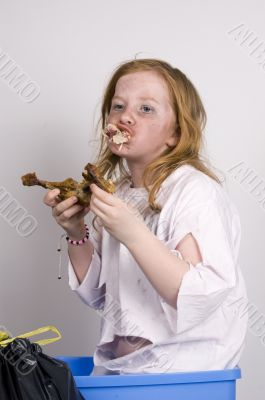 homeless girl is eating a piece of chicken