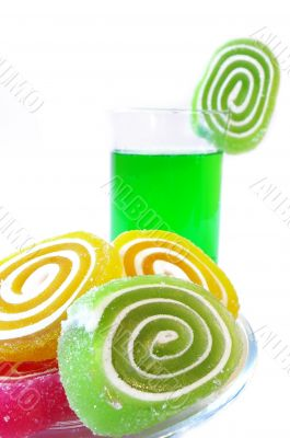 Multi-coloured fruit candy  and cold green drink