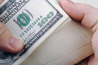 Man Fanning Large Stack of One Hundred Dollar Dollar Bills