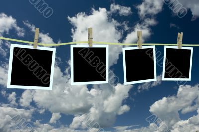 Four clean photos hanging on a cord. 3D image.