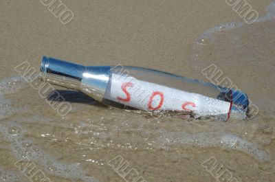 Message in a bottle with SOS signal lying in surf