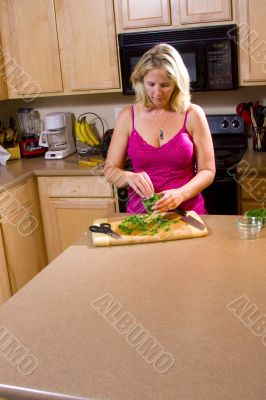 Blond woman cutting food in kitchen