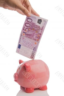 Saving a note of five hundred euros in a piggy-bank