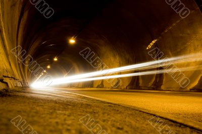 lone car moving fast in tunnel