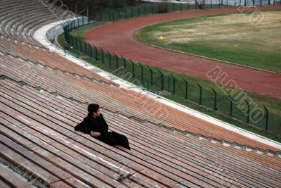 one man sitting alone in stadium grandstand