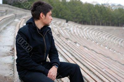 cool man sitting alone in stadium tribun