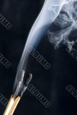 match with smoke on black background