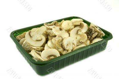 Sliced champignon mushrooms in green pack