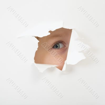 Eye looking through hole in sheet of paper