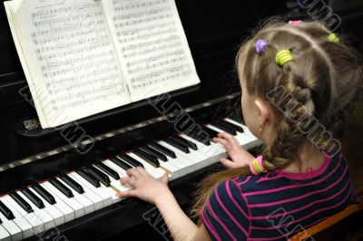 child plays on piano, lesson of the music