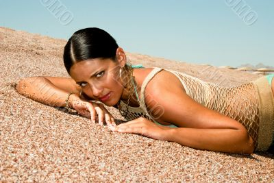 The model poses on a beach