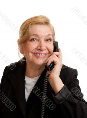 Senior Woman talking on the phone in black suite.