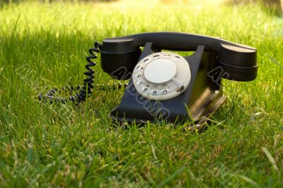 Retro styled rotary telephone in the grass
