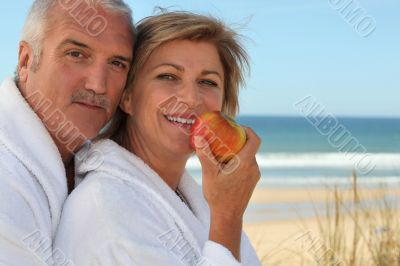Mature couple in bathrobes on the beach