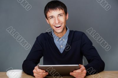 Closeup of a young smiling business man sitting at his office agagainst gray wall and using his modern tablet pc to do his work.