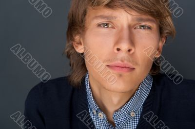 Portrait of young man with smart and wise look. Looking at camera.