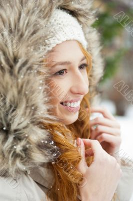 Portrait of pretty girl at winter background wearing warm clothes.