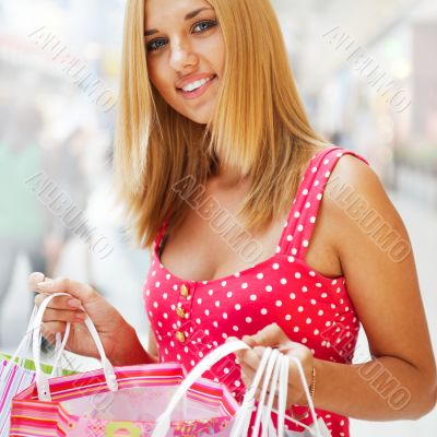 Beautiful woman at a shopping center with bags and smiling