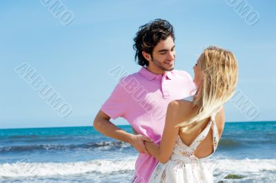 Young couple at beach, embracing, side view. Natural emotions. H