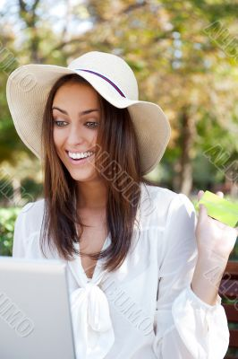 Young elegant woman wearing straw hat and white dress holding cr