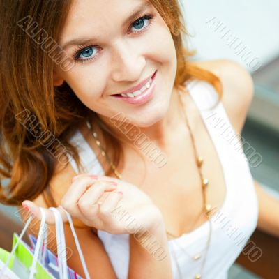 Happy shopping woman with bags and smiling. She is shopping insi