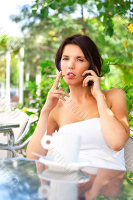 Portrait of a phoning woman sitting relaxed at outdoors cafe and