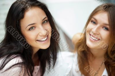 Two women whispering and smiling while shopping inside mall
