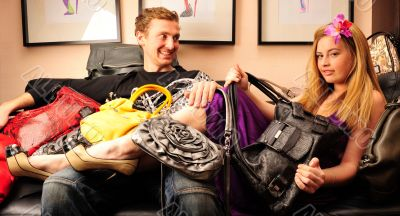 Smiling fashionable rich attractive couple sitting on sofa at ho