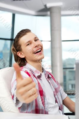 Happy satisfied young man sitting relaxed on his armchair and th