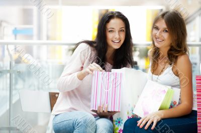 Two excited shopping woman resting on bench at shopping mall loo