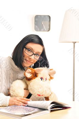 Closeup portrait of a young woman embracing her soft toy