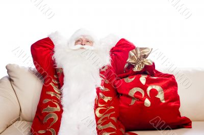 Traditional Santa Claus resting on sofa indoors and daydreaming.