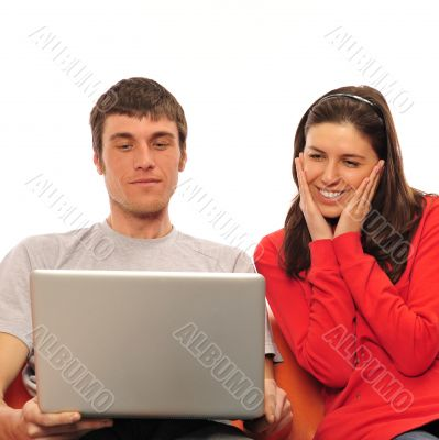 Young romantic couple sitting on their sofa and enjoying fast wi