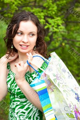 Beautiful woman walking at the summer park holding bags and look