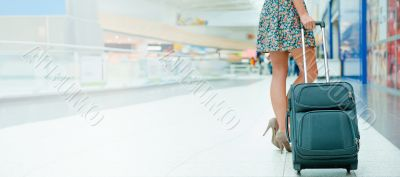 Woman`s legs and travel suitcase at international airport tax fr